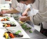 chef plating up in busy restaurant