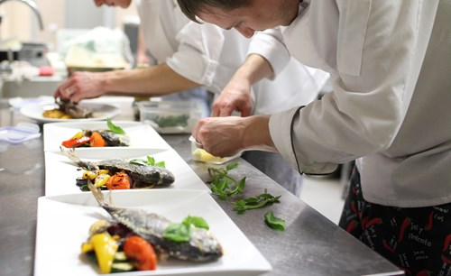 Chef plating up in professional kitchen