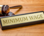 Minimum wage sign on wooden desk with gavel