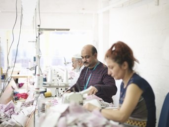 Two men and a women sewing clothes
