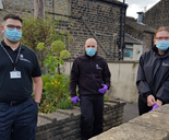 One female two male GLAA investigators wearing PPE outside terrace house