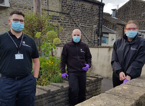 Three GLAA officers outside a terrace house wearing PPE masks and gloves